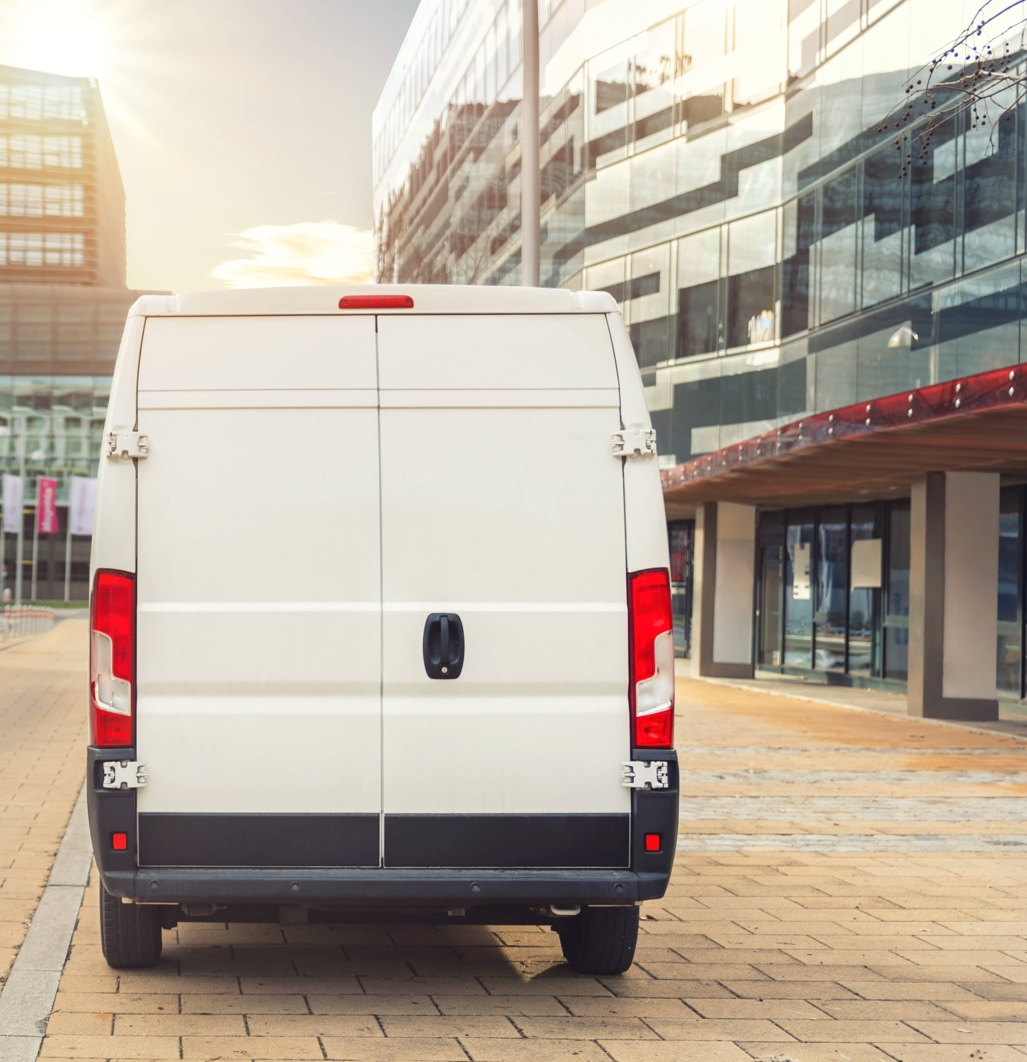 Small cargo delivery van driving in european city central district. Medium lorry minivan courier vehicle deliver package at residential office building in downtown area. Commercial shipping logistics.