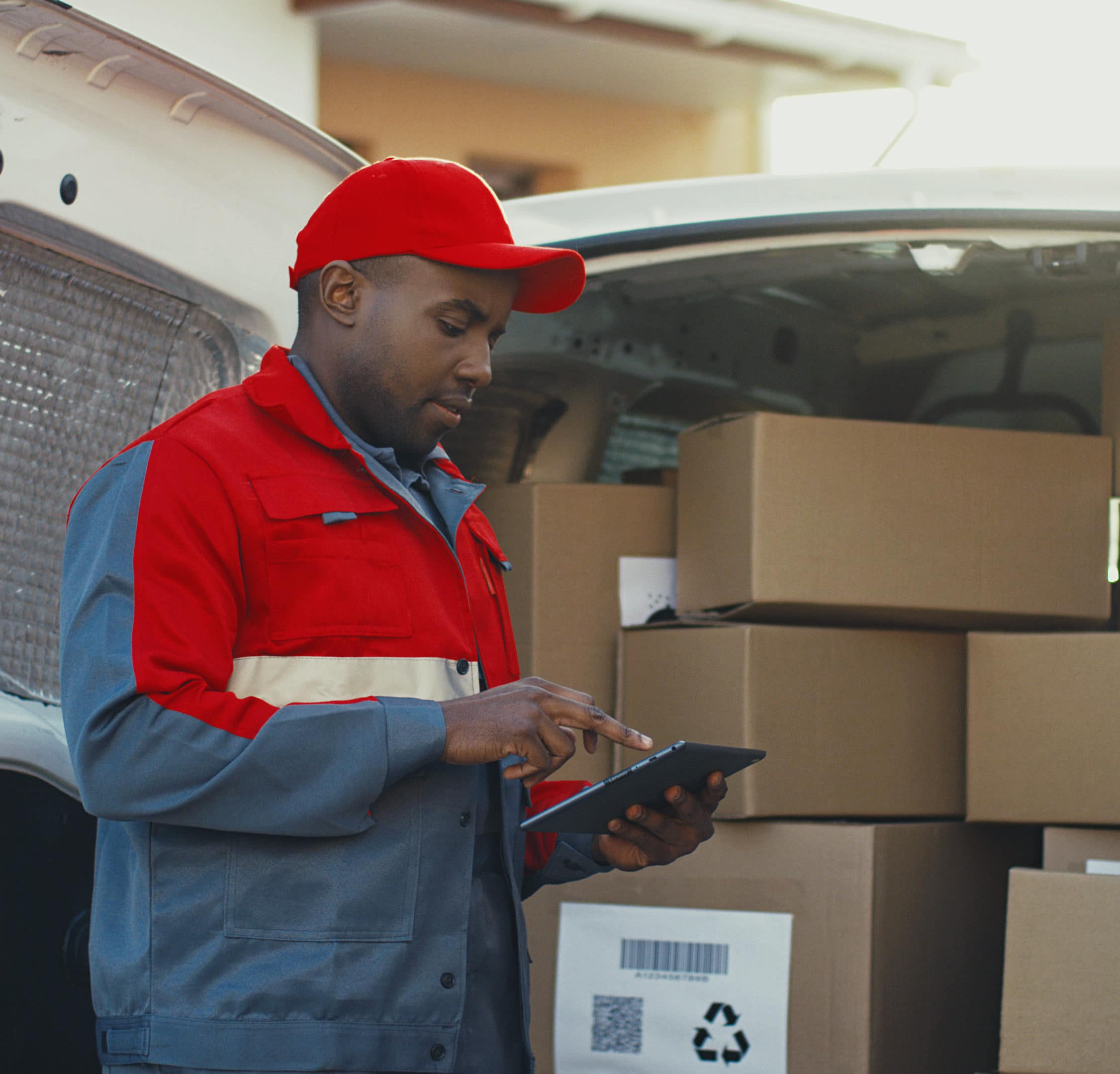 African American young mailman in red costume and cap counting the mail boxes in a van with tablet device in hands. Outdoors.
