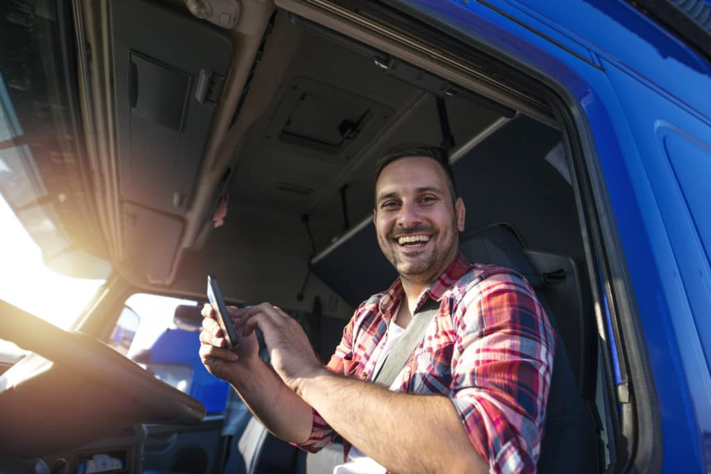 Truck driver with tablet using GPS navigation for his route. Transportation services.
