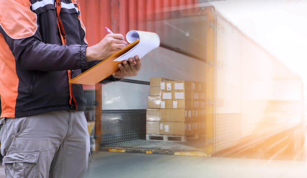 Warehouse worker holding clipboard with control loading shipment goods into container truck. Road freight cargo shipping logistics and transportation.